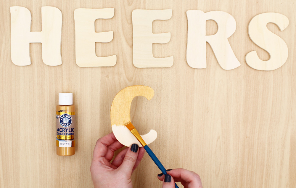 Paint wood letters with gold paint. Let dry.